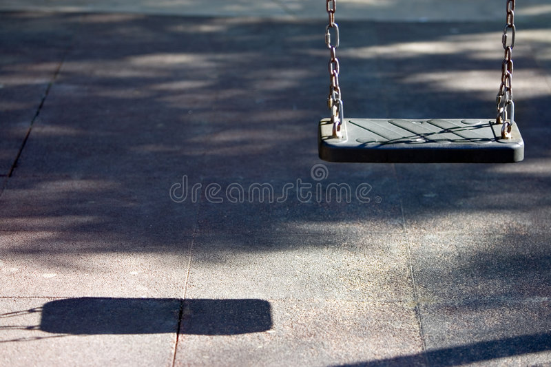 Single swing seat and shadow in playground. Single empty swing seat and shadow in childrens playground stock photos