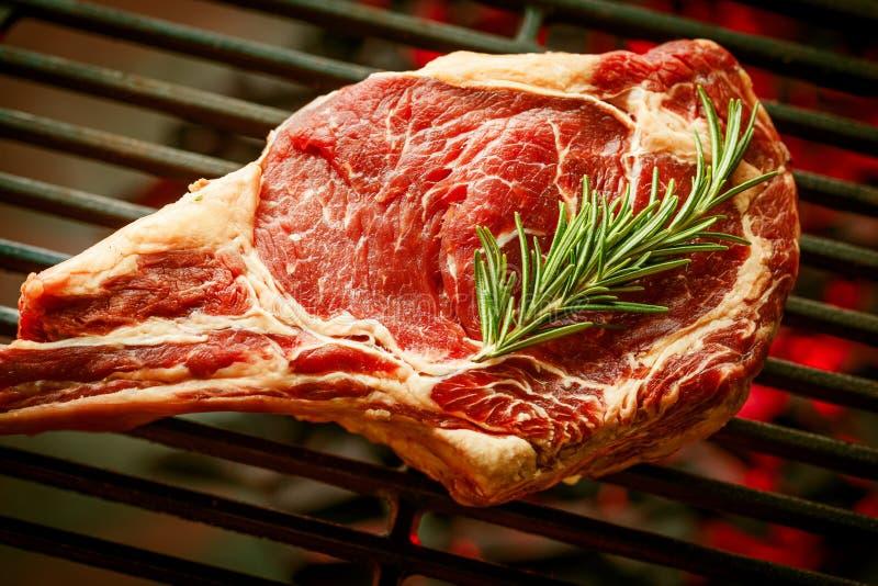 Single tomahawk rib steak on hot black grill . royalty free stock image