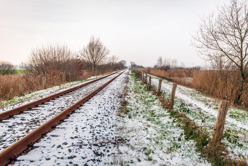 Single-track ράγες σε ένα χειμερινό τοπίο που καλύπτεται με ένα στρώμα του χιονιού στοκ εικόνες