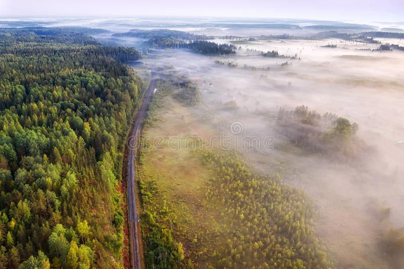Single track railway through the misty woodland aerial view. At summer morning royalty free stock image