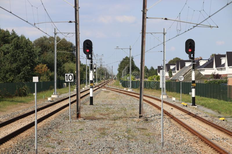 Single track with red signs which splits at the platforms of station Boskoop in the Netherlands for track between Gouda and Alphen stock photography