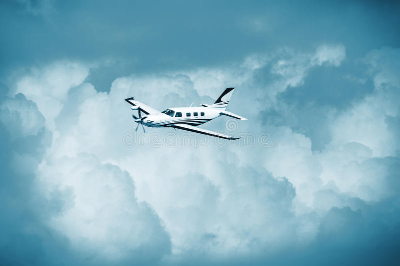 Single turboprop aircraft.. Small private plane flying in blue clouds. Single piston aircraft. Single-propeller aircraft flying over the blue sky. Single royalty free stock photo