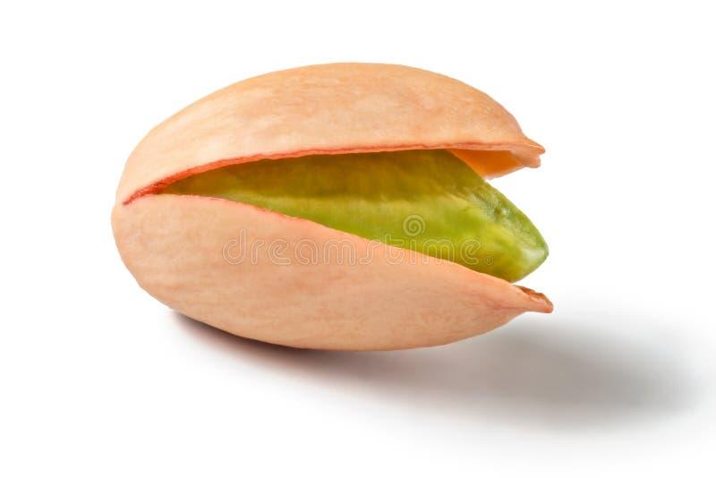 Single Turkish red pistachio, peeled green nut visible, isolated on white background.  stock photo