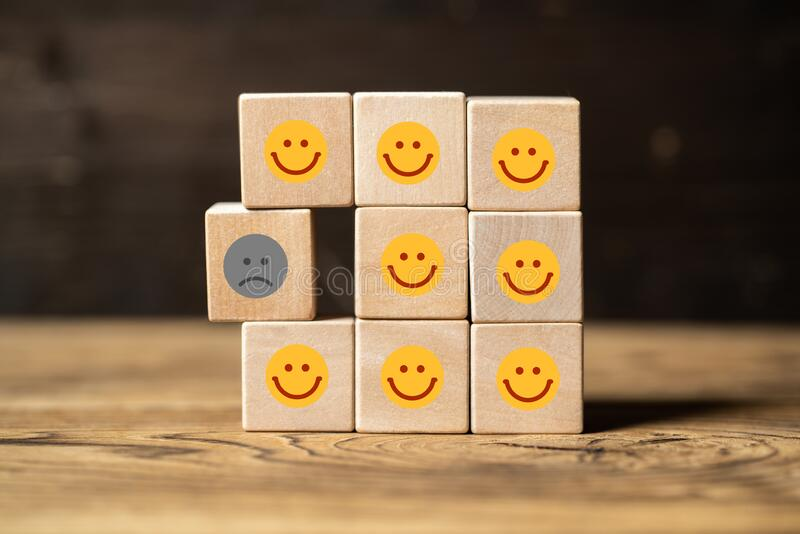 Single unhappy block and group of happy blocks. Symbolizing feeling lonely on wooden background royalty free stock photos