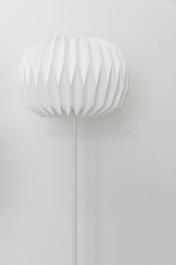 The single unique round shape paper electric floor lamp on white wall background. Single unique round shape paper electric floor lamp on white wall background royalty free stock images