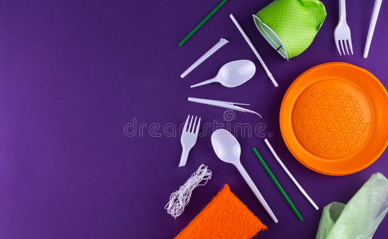 Single-use plastic objects, ecological pollution. Plastic waste. Orange, white and green packaging plastic products, top view flat. Lay border frame with copy stock images