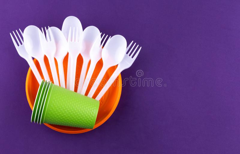 Single-use plastic objects, ecological pollution. Plastic waste. Orange, white and green packaging plastic products, top view flat. Lay border frame with copy royalty free stock image