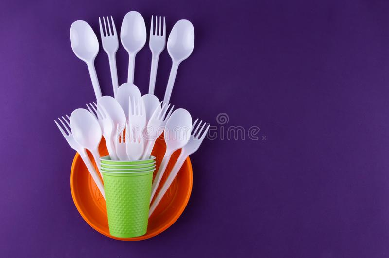 Single-use plastic objects, ecological pollution. Plastic waste. Orange, white and green packaging plastic products, top view flat. Lay border frame with copy stock photography