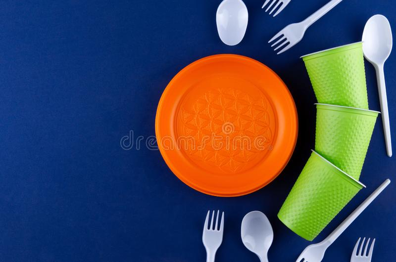 Single-use plastic objects, ecological pollution. Plastic waste. Orange, white and green packaging plastic products, top view flat. Lay border frame with copy stock photo