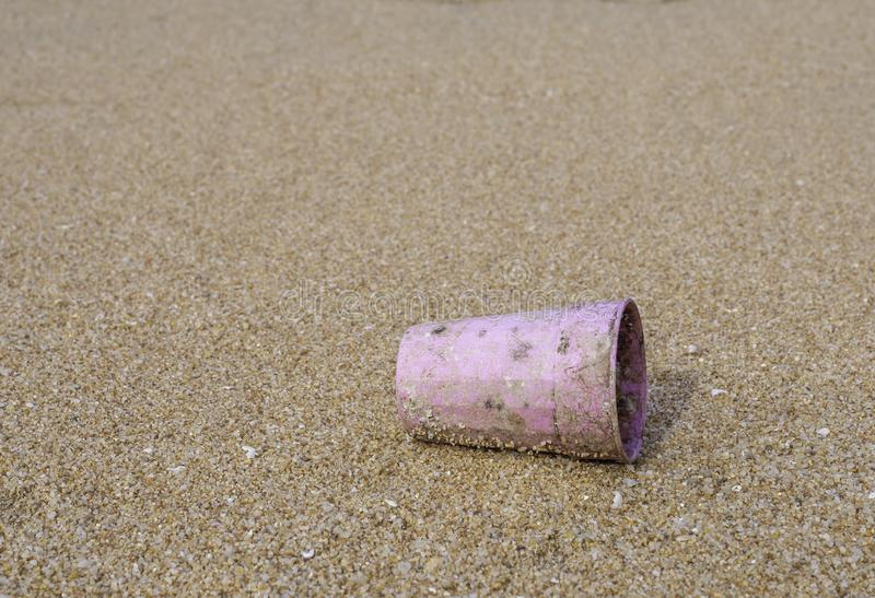 Single use plastic pink cup littering on the beach with sand blurred background, close up. Single use plastic pink cup littering unclean on the beach with sand royalty free stock image