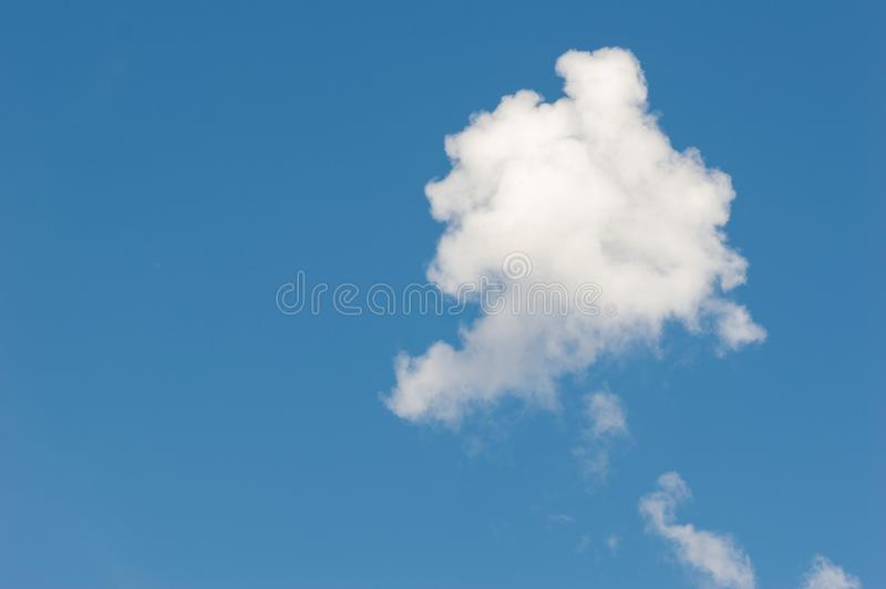 A single white cloud in the blue sky. Isolated cloud in blue background stock photos