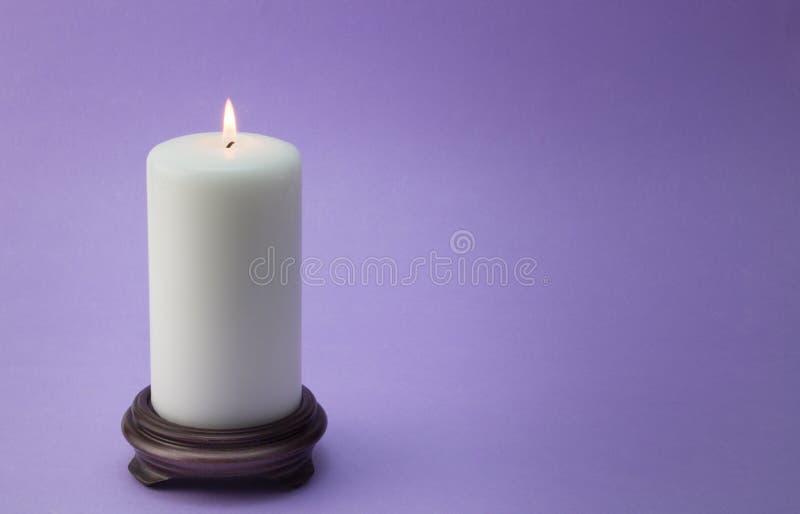 Single white lit candle on wood holder on lilac / mauve. Background stock images