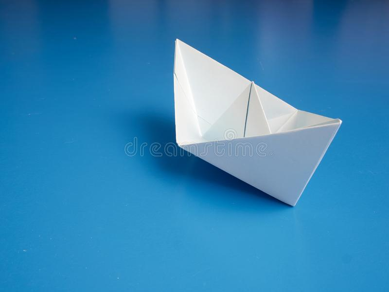 Single white paper boat on a blue background royalty free stock photography