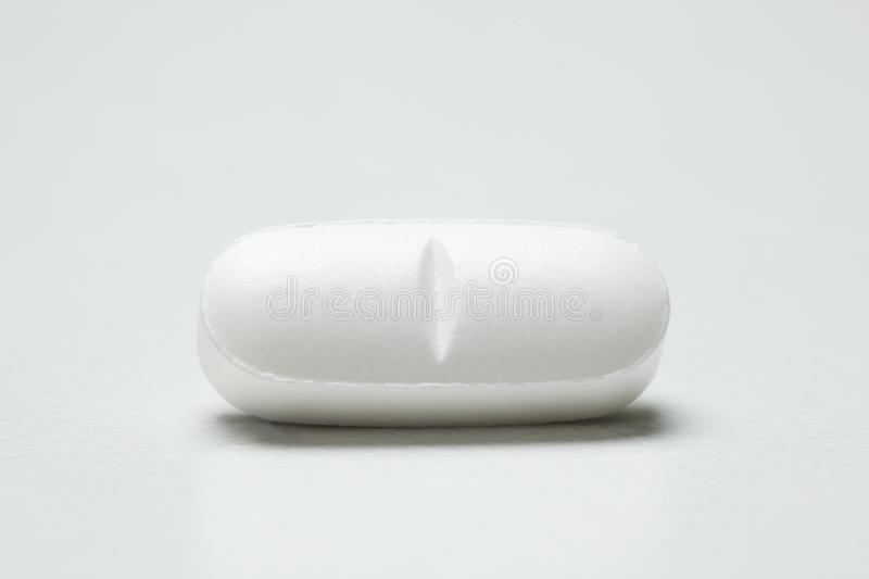 Single white pill. Single pill against white background royalty free stock photography