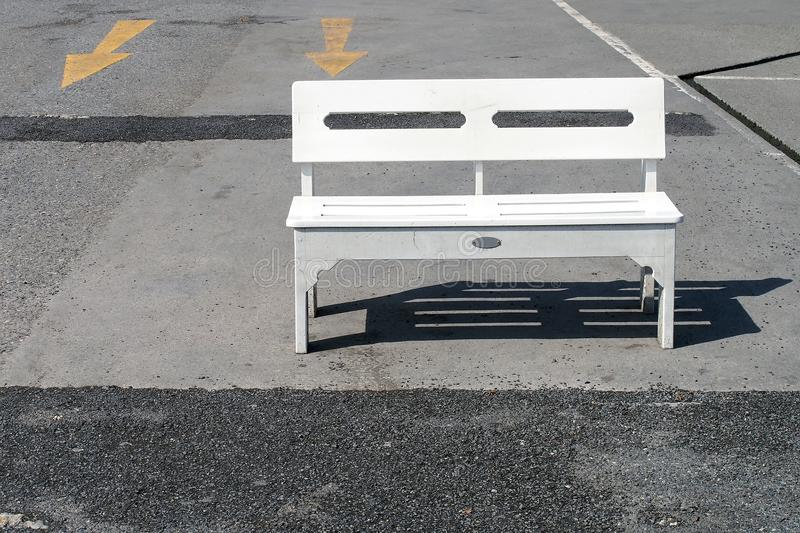 single white wooden bench is placed in afternoon sunlight on concrete floor of empty car park royalty free stock images