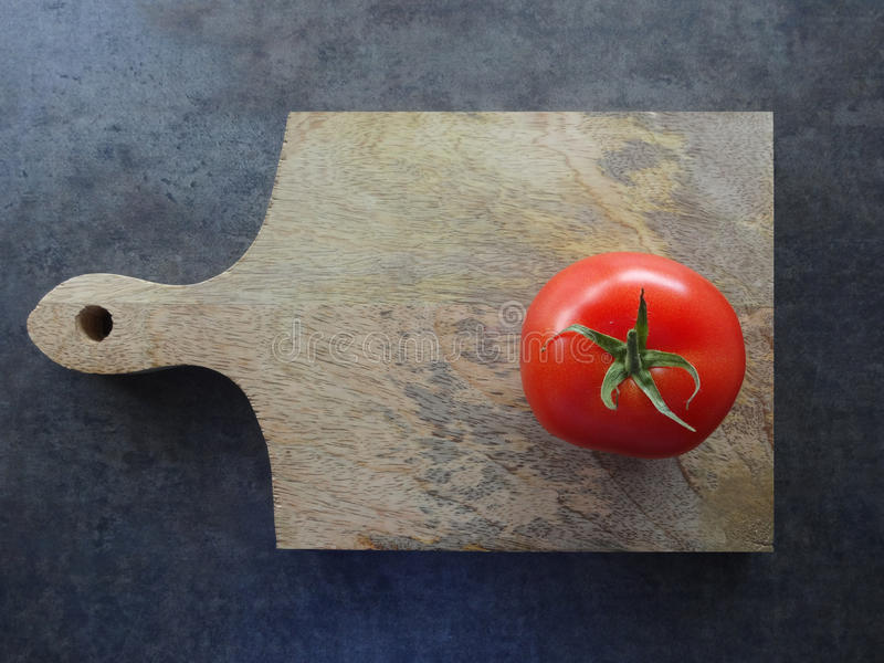 Single Whole Vine-Ripe Tomato. A Single Whole Vine-Ripe Tomato on a Rustic Wooden Cutting Board against a Gray Background stock photography