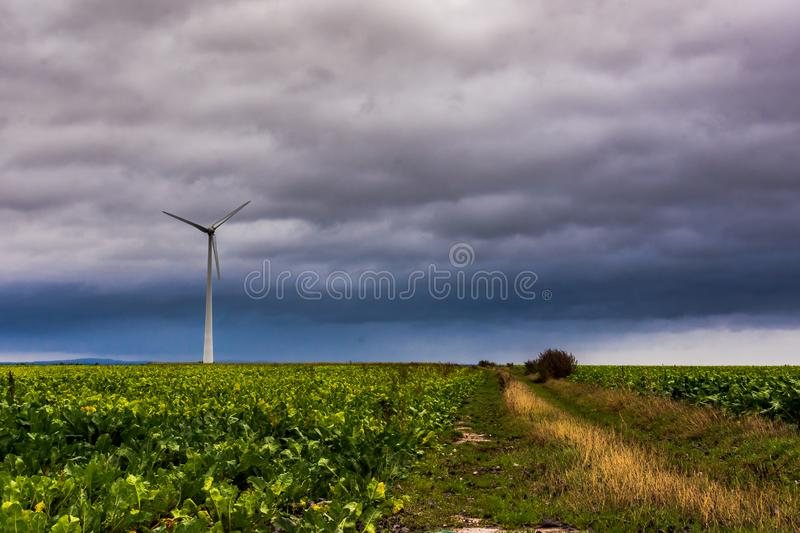 Single Wind turbine in green field against dramatic cloudy sky, France stock photography