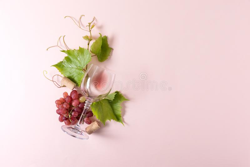 Single wineglass with rose wine, grape, leaves and cork lying on pink background. Wine degustation concept. Flat lay. Top view. Copy space royalty free stock image