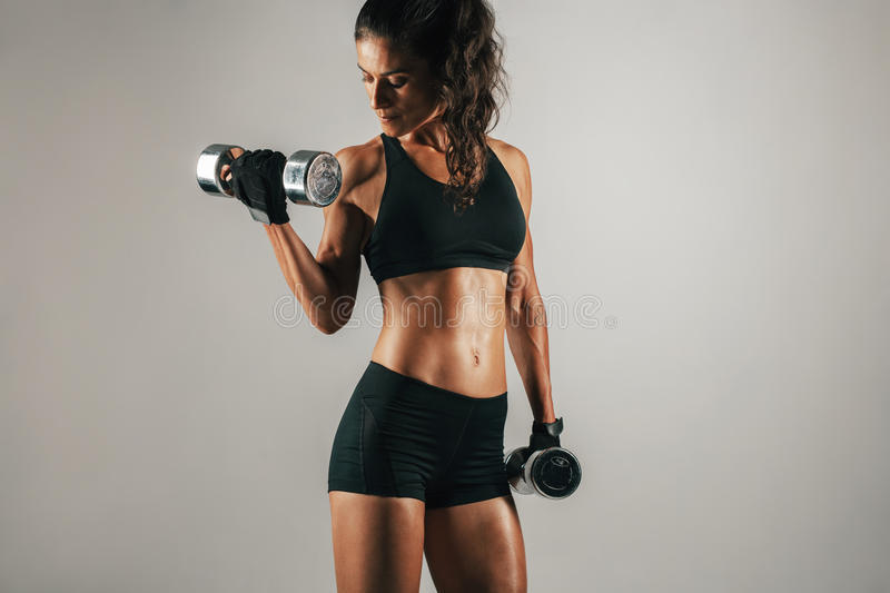 Single woman lifting weights over gray background. Single athletic woman lifting chrome finish dumbbell weights over gray background with copy space royalty free stock photo