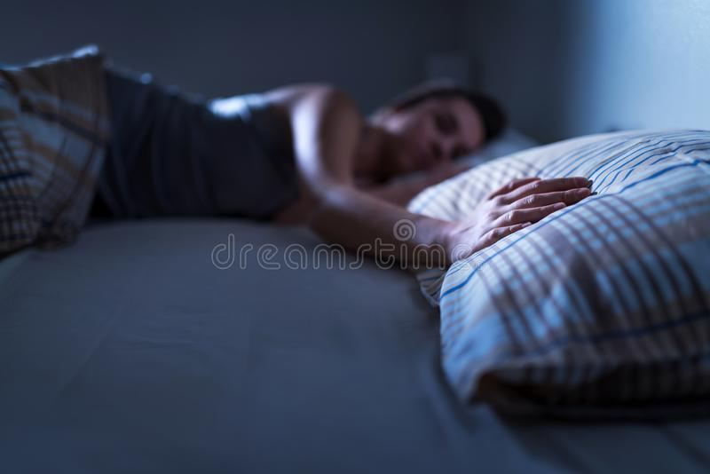 Single woman sleeping alone in bed at home. Lonely lady missing husband or boyfriend. Hand on pillow. royalty free stock image
