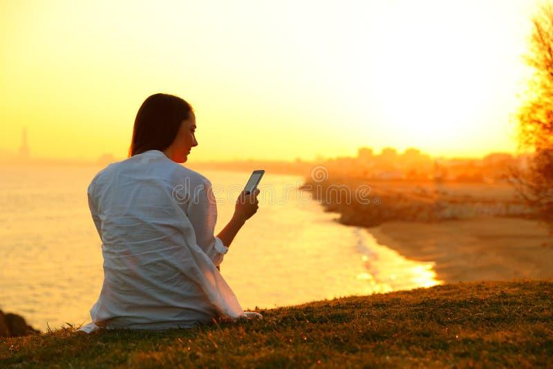 Single woman using a smart phone at sunset stock image