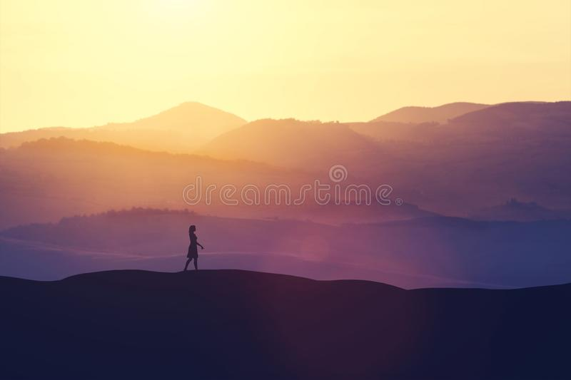 Single woman walking on the hill during sunset. royalty free illustration