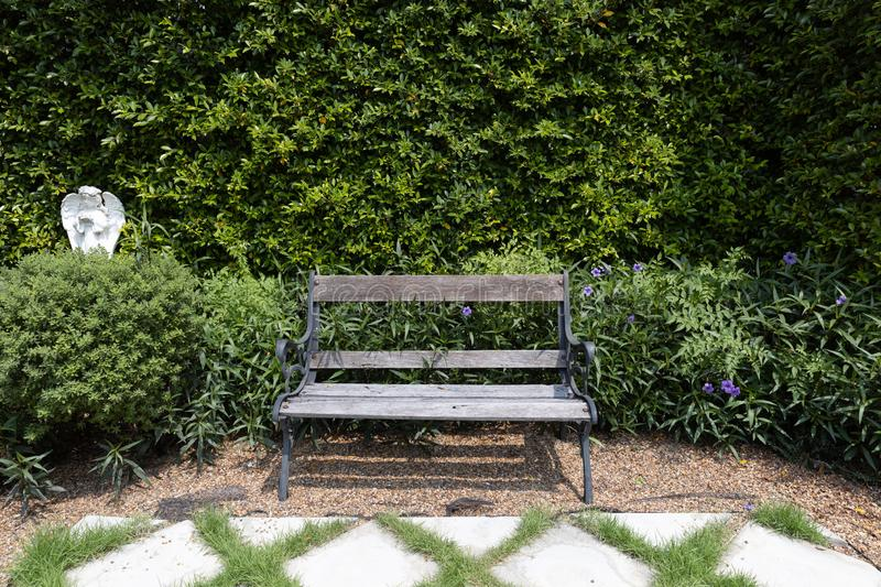 Single wooden bench chair with stone grid walkway pavement and pebble or gravel in exterior garden royalty free stock photo