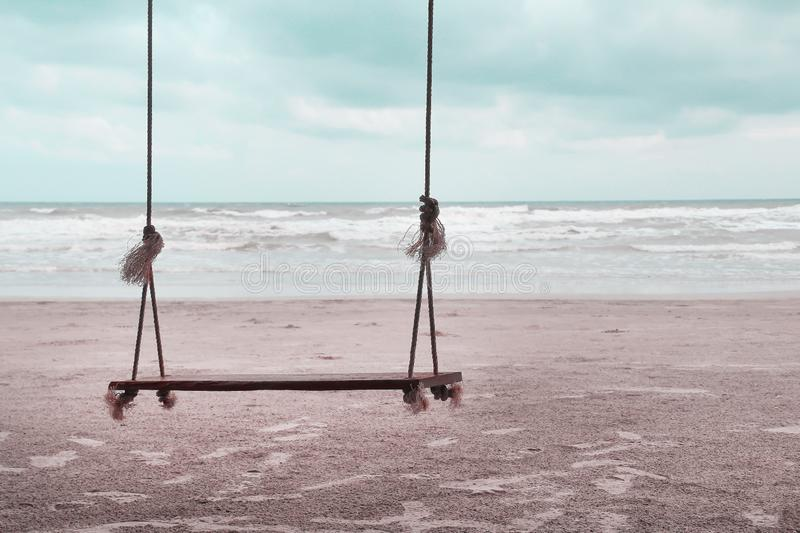 Single wooden swing with soft wind and landscape beach , natural sea background stock photo