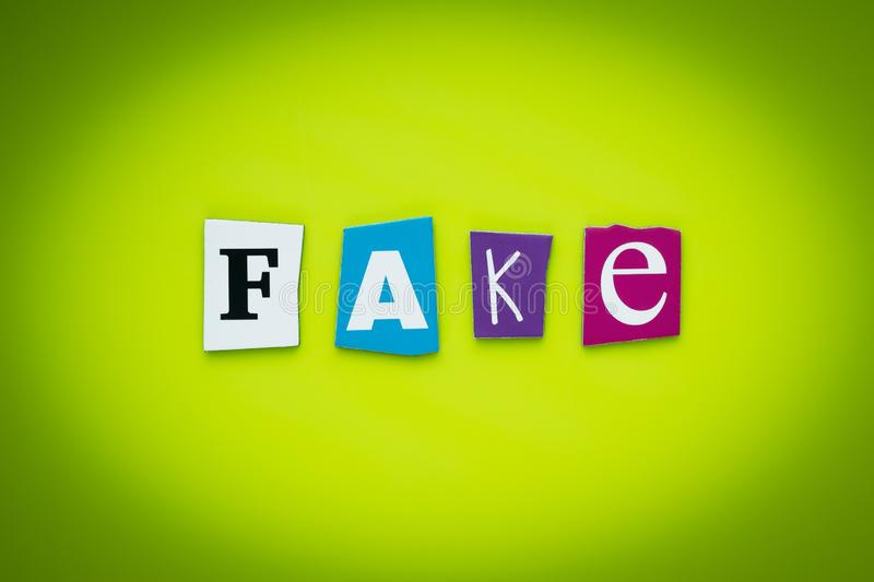 Single word - fake. Text on yellow and green background. Message on poster. Cutted colorful letters. Headline on bright card. Multicolor inscription on banner stock images