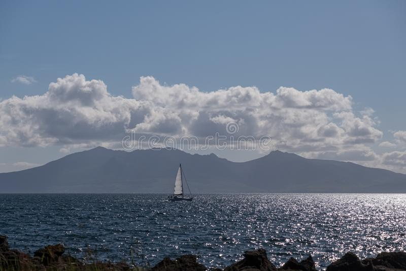A single yacht with a white sail sailing in front of The Isle of Arran on the River Clyde in Scotland on the Summer Solstice. A single yacht,, with a white sail royalty free stock photo
