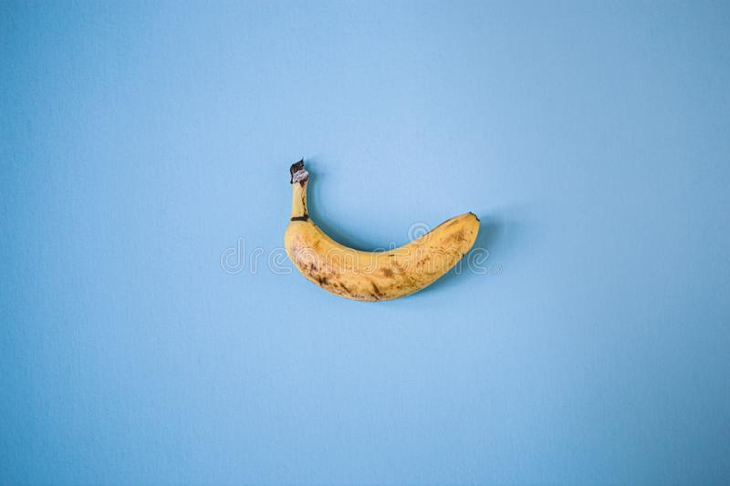 Single yellow banana on a blue background royalty free stock image
