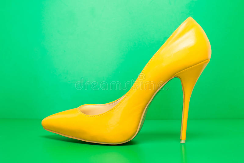 Single yellow high heels. Singel yellow high heels on green background stock image