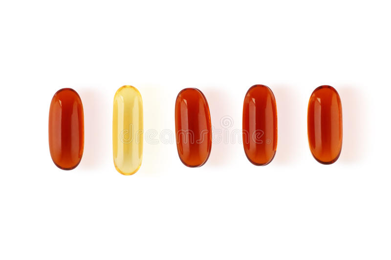 A single yellow pill in a row of orange pills. A single yellow pill in a row of orange pills, a concept of individuality and diversity. Isolated on a white royalty free stock images