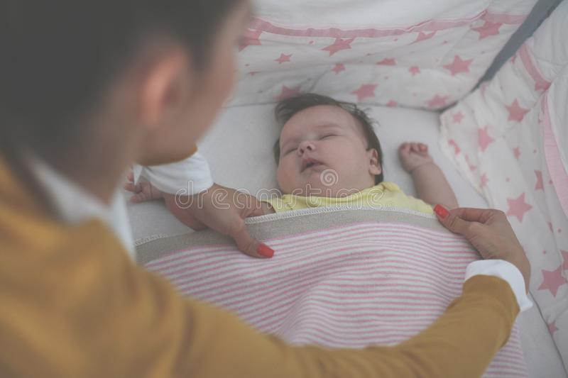 Single young mother is sleeping her baby. Close up. From above stock photography