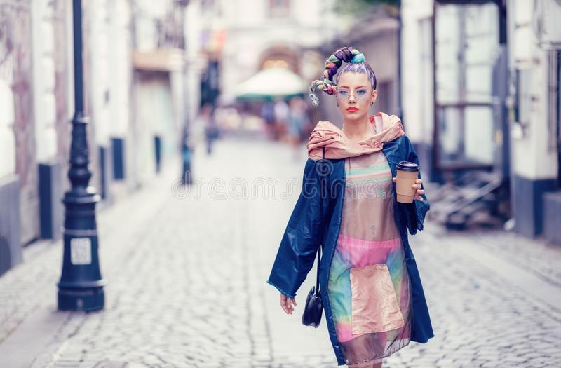 Single edgy girl with extravagant look on streets. Crazy appearance on boulevard. Avant-garde fashion concept stock images
