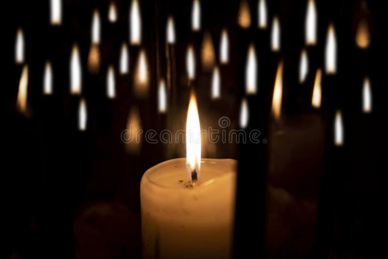 Singola candela e molte fiamme fotografia stock libera da diritti