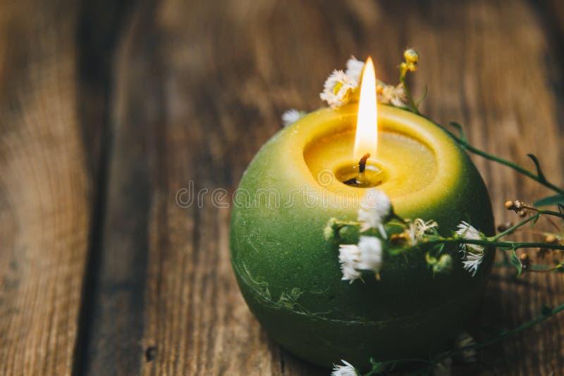 Singola candela a forma di palla verde con un fiore asciutto che brucia su un primo piano di legno rustico della tavola fotografia stock libera da diritti