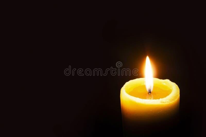 Singola candela gialla bruciante che emette luce su un fondo scuro Copi lo spazio fotografia stock libera da diritti