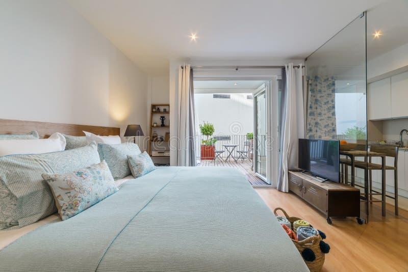 Singola casa moderna della camera da letto con la piccola cucina fotografia stock libera da diritti