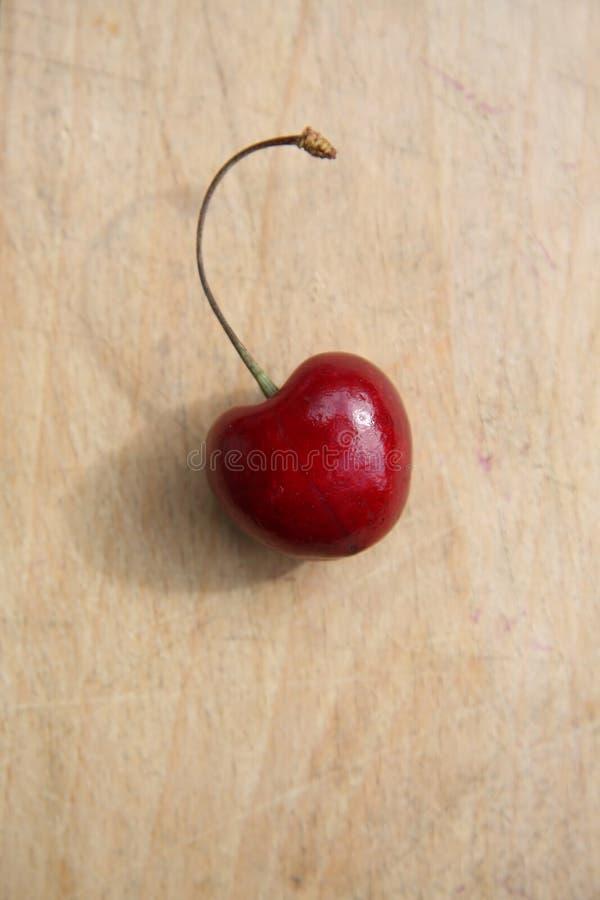 Singola ciliegia su legno fotografia stock