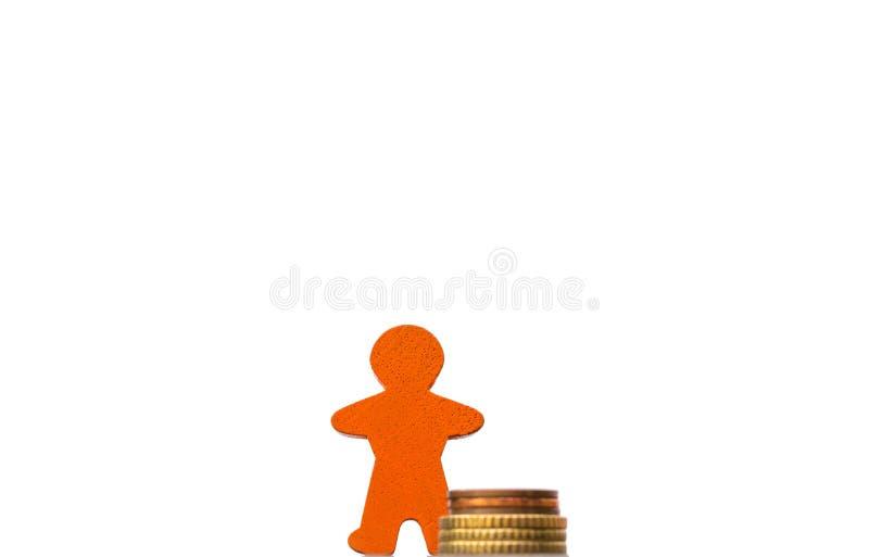 Singola figura di legno con le monete davanti a fondo bianco come segno della capacità finanziaria di un individuo fotografia stock