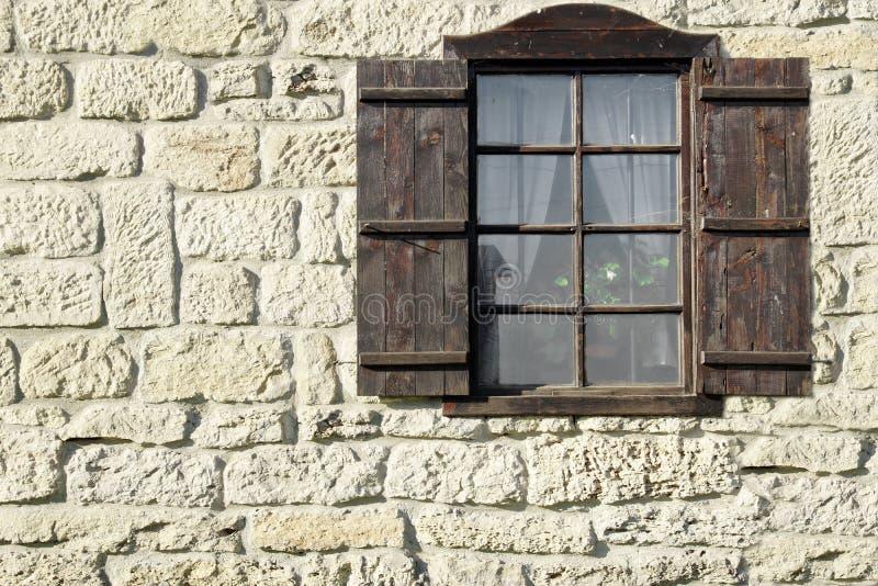 Singola finestra d'annata con gli otturatori di legno su Wal di pietra naturale fotografie stock