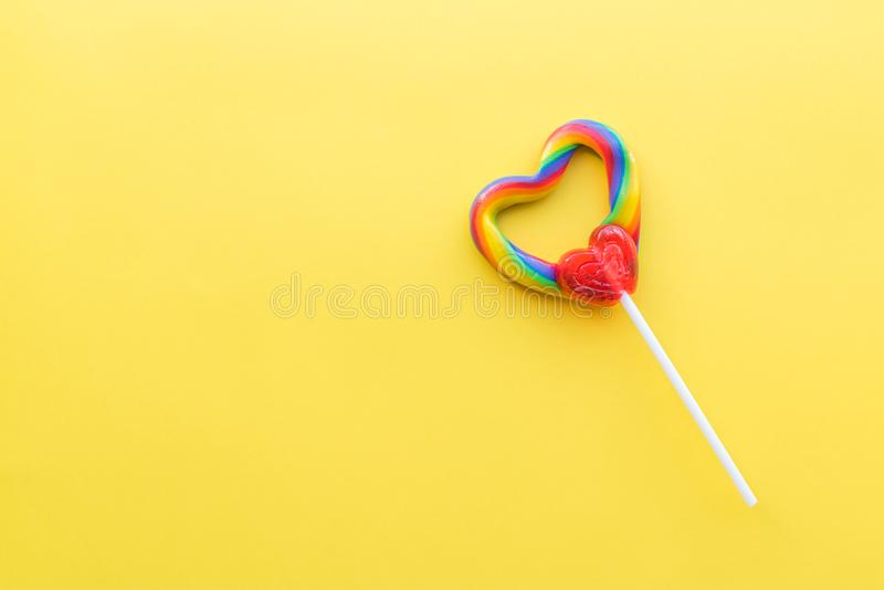 Singola lecca-lecca in forma di cuore con i colori di turbinio dell'arcobaleno con fondo giallo luminoso fotografia stock