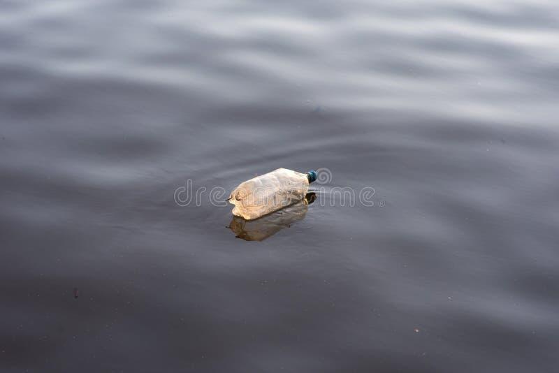 Singola lettiera di plastica della bottiglia di acqua che galleggia in acqua del lago fotografia stock libera da diritti