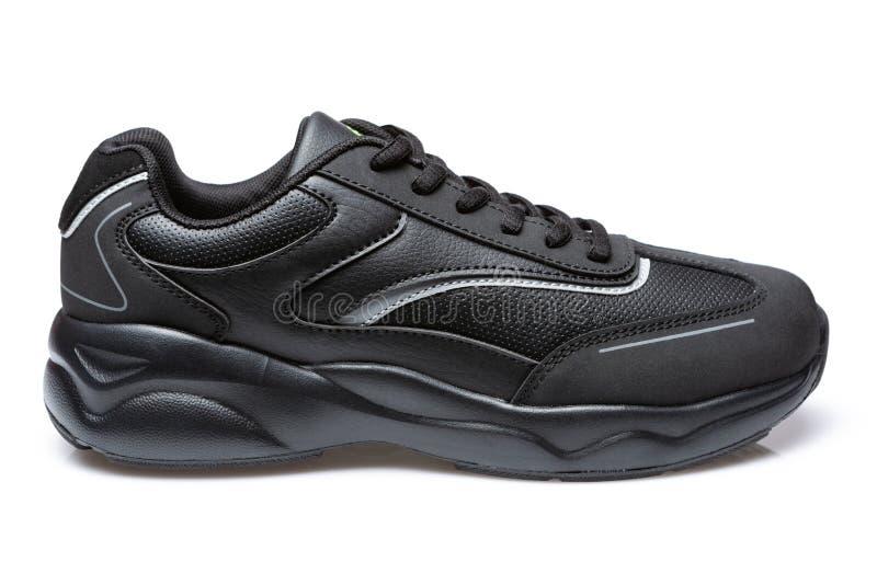 Singola scarpa da tennis nera con la sogliola spessa, concetto, su un fondo bianco immagine stock