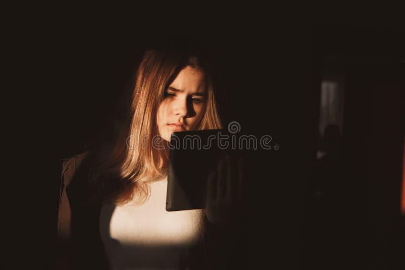 Singola tenuta teenager triste un telefono cellulare che deplora seduta sul letto nella sua camera da letto con una luce scura immagini stock libere da diritti