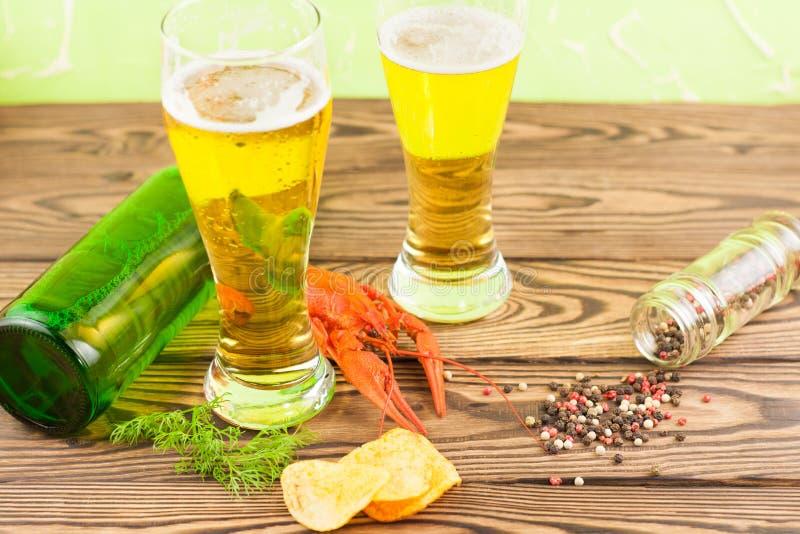 Singoli gambero bollito rosso vicino a due vetri pieni di birra con schiuma ed al ramoscello di aneto verde fresco e delle patati fotografie stock libere da diritti
