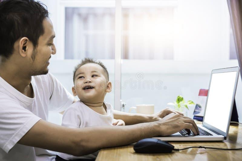 Singoli papà e figlio che per mezzo insieme del computer portatile felicemente tecnologia e immagine stock