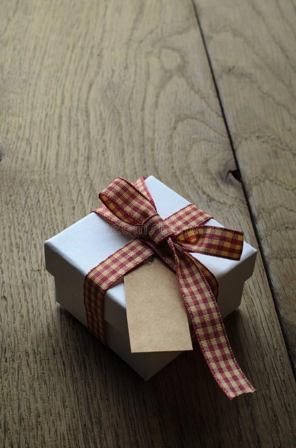 Singolo contenitore di regalo con il nastro del percalle ed etichetta in bianco su legno fotografia stock
