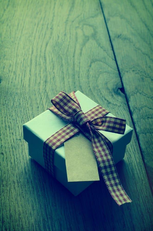 Singolo contenitore di regalo con il nastro del percalle ed etichetta in bianco su legno - Cr fotografia stock